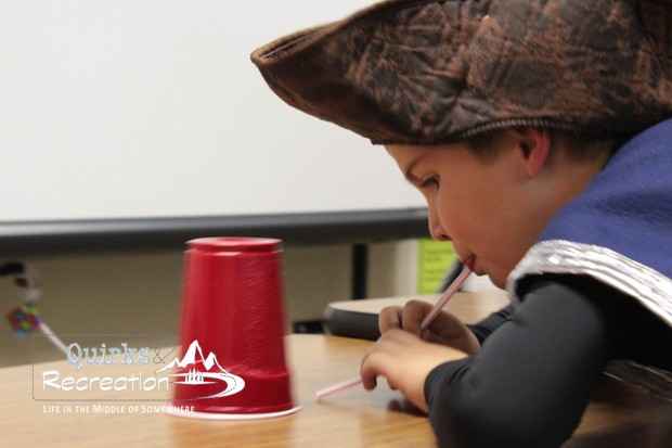 boy blowing a cup with a straw at a fall festival