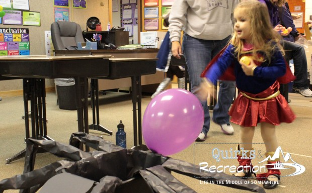 girl dressed in costume throwing a balloon at a fall festival
